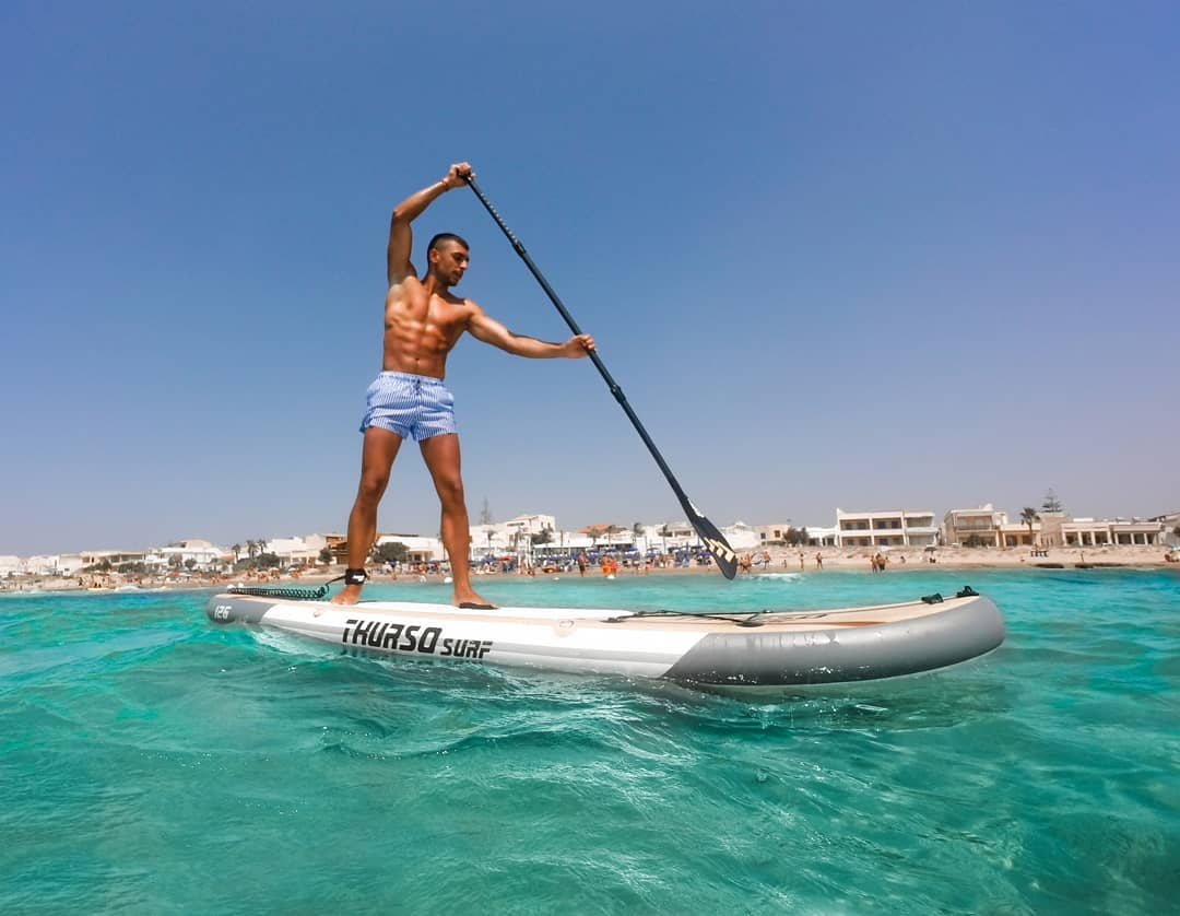 man paddles Thurso Surf Waterwalker all-around iSUP near beach