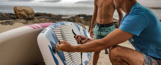 Father explains dos and don'ts of paddleboard care to son