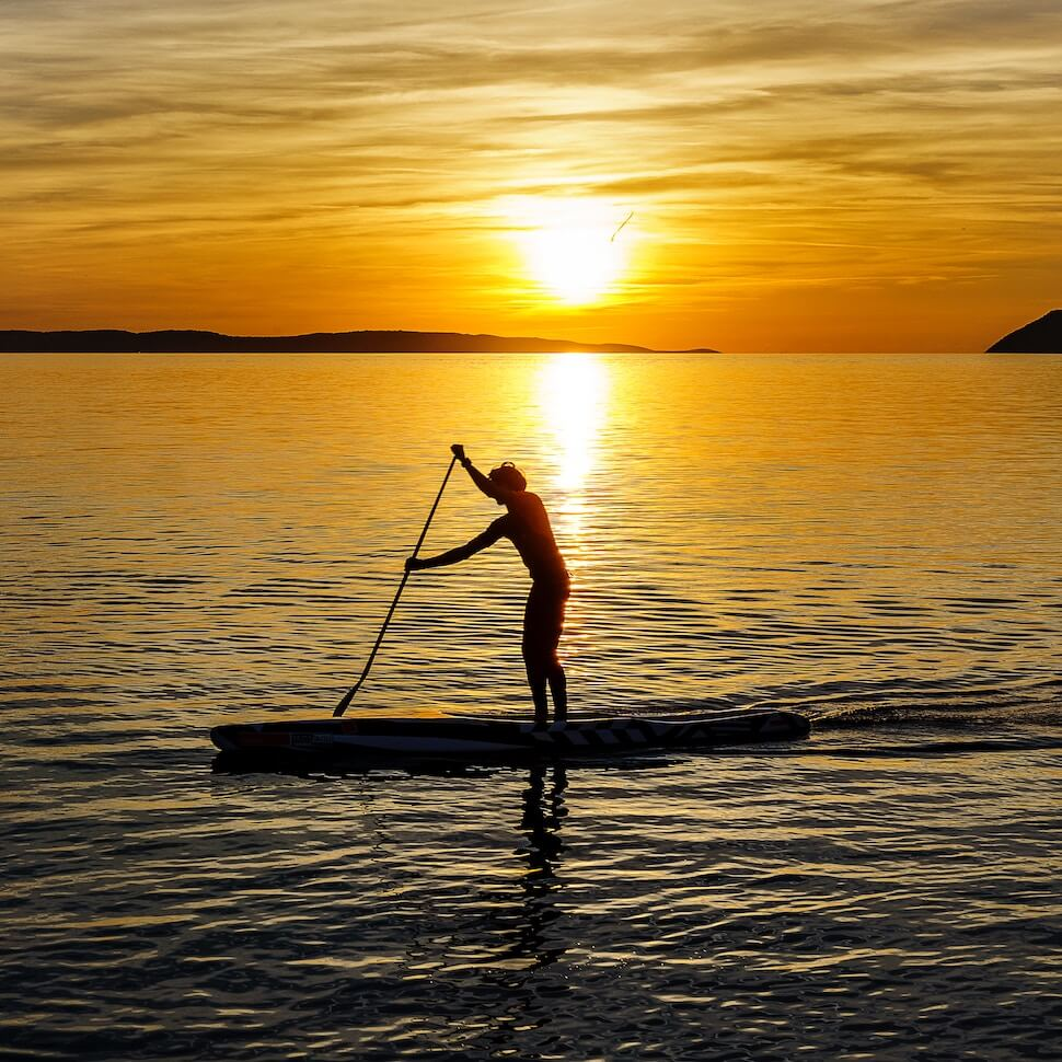 person stand up paddleboards during sunset