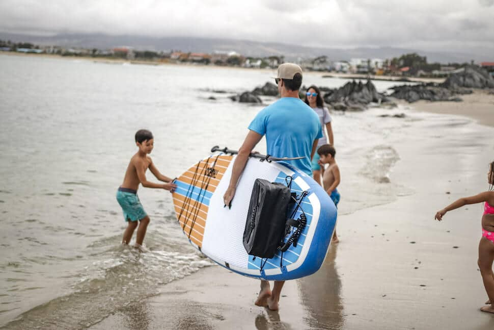 Family walking along beach with father carrying Thurso Surf Max multi-purpose SUP with paddle attached