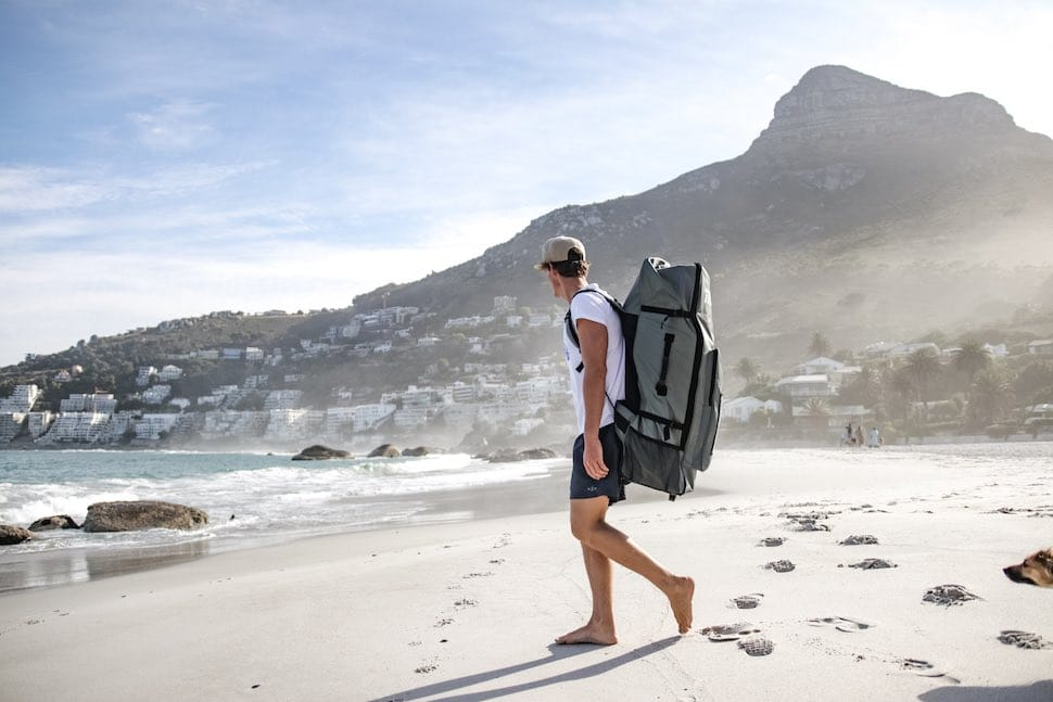 Man walks along beach with Thurso Surf Roller Backpack