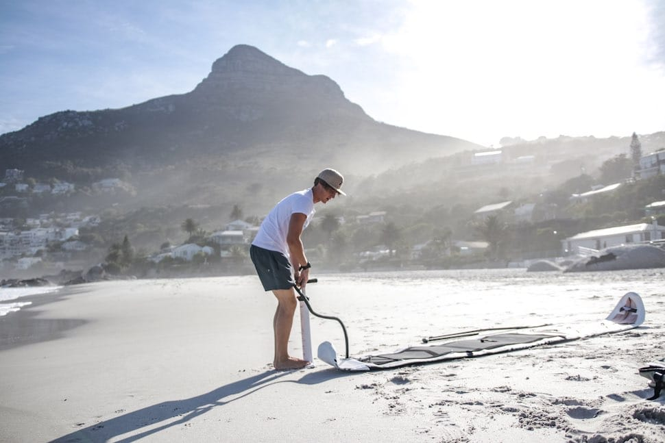 Man inflates his Thurso Surf Expedition Touring SUP on the beach