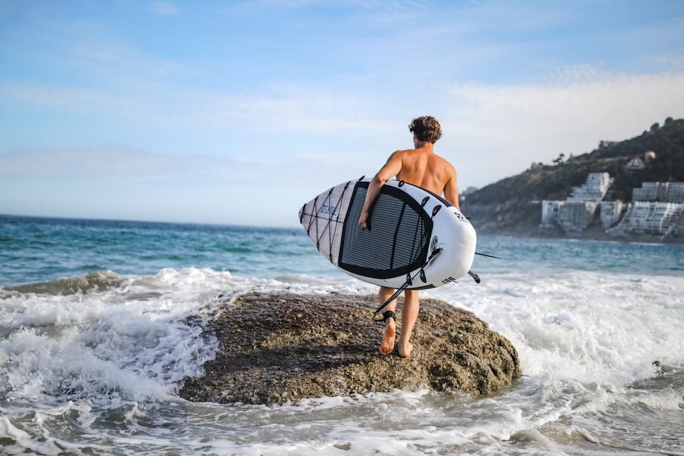 Man with SUP heading out for a beach body workout