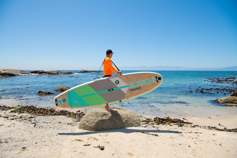 Man stands with Thurso Surf Waterwalker All-around SUP on rock overlooking beach