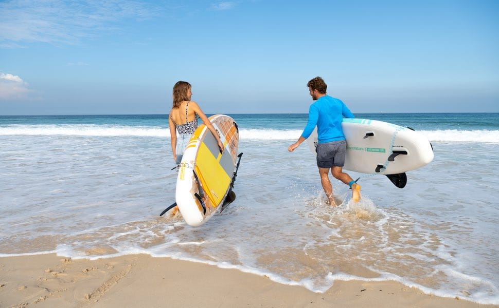Man and woman run into wave with Thurso Surf Waterwalker All-around SUP