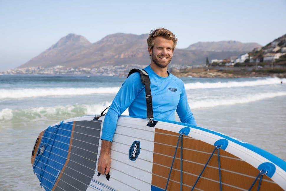 Man using should strap walks with Thurso Surf Max Multi-purpose SUP