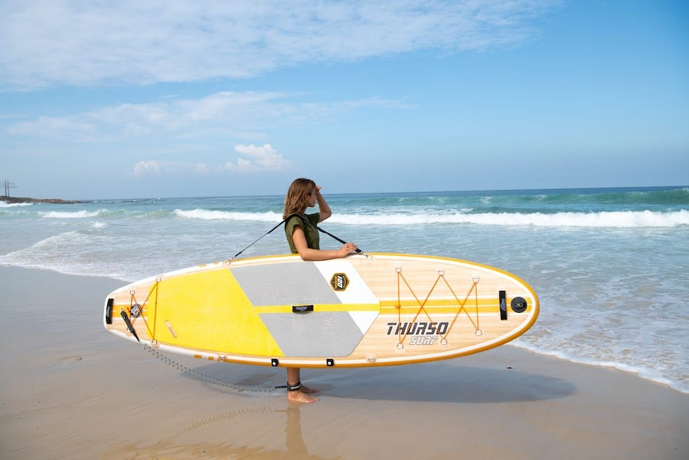 Woman looks out over water using shoulder strap on Thurso Surf Waterwalker All-around stand up paddleboard