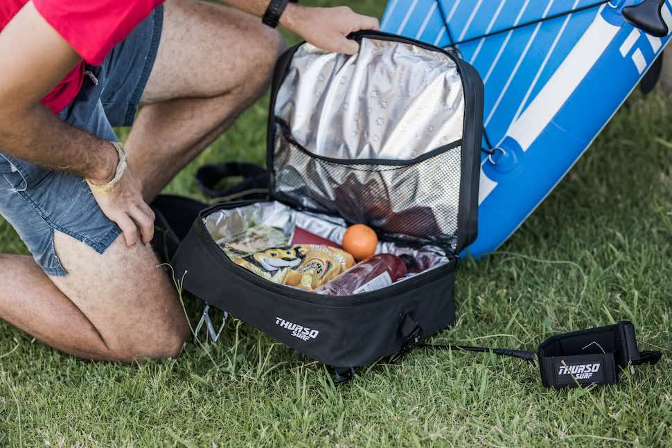 Kneeling man packs deck cooler page for stand up paddleboard fishing