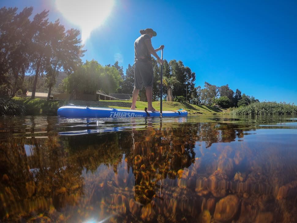 Man paddles shallow river on Thurso Surf Max multi-purpose SUP