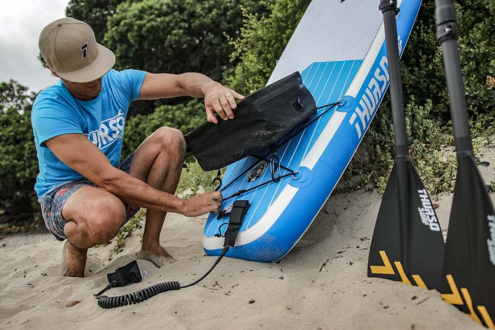 Squatted man attaches bag to SUP for a stand up paddleboard fishing adventure