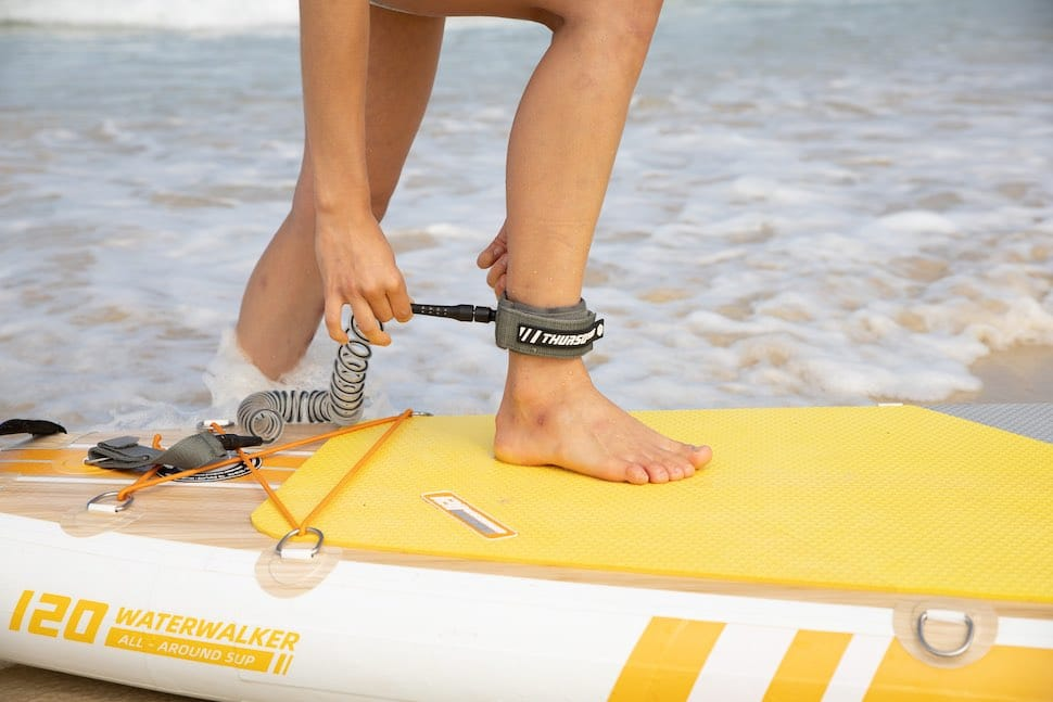 Close up of woman attach attaching ankle leash which is not a piece of stand up paddle clothes but essential to wear