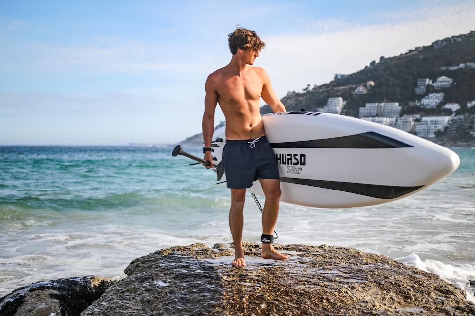 Man standing on rock holding SUP only wearing board shorts for his stand up paddle clothes
