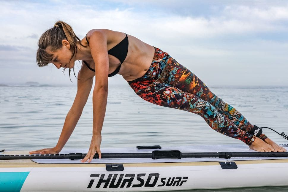 Woman wearing yoga pants and top for stand up paddle clothes while practicing on her Thurso Surf Tranquility yoga SUP