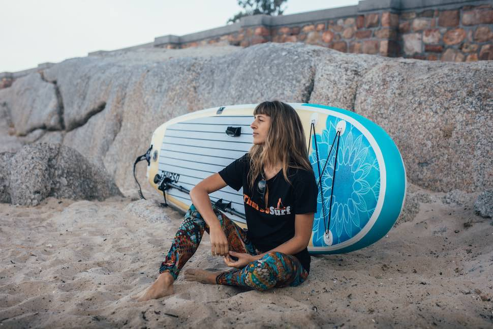 Best women's paddle board for yoga, the Thurso Surf Tranquility Yoga SUP leans on rocks