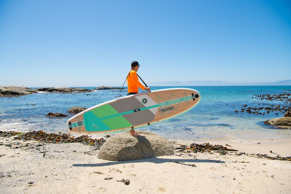 man shows how to transport a paddle board using a Thurso Surf shoulder carry strap