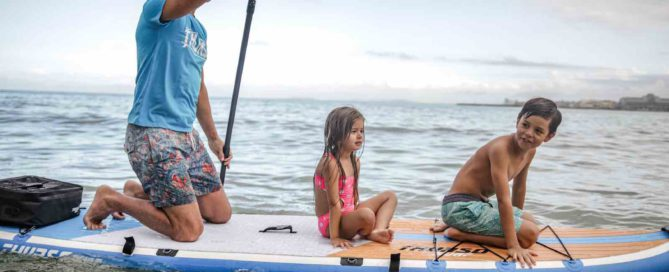 man paddles from knees with two children sitting on the stand up paddleboard traction pad