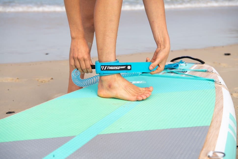 Following basic SUP surfing safety woman attaches ankle leash before going into waves.