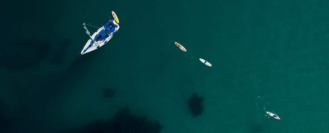 Overhead drone shot image of four stand up paddle boards paddling away from a sailboat