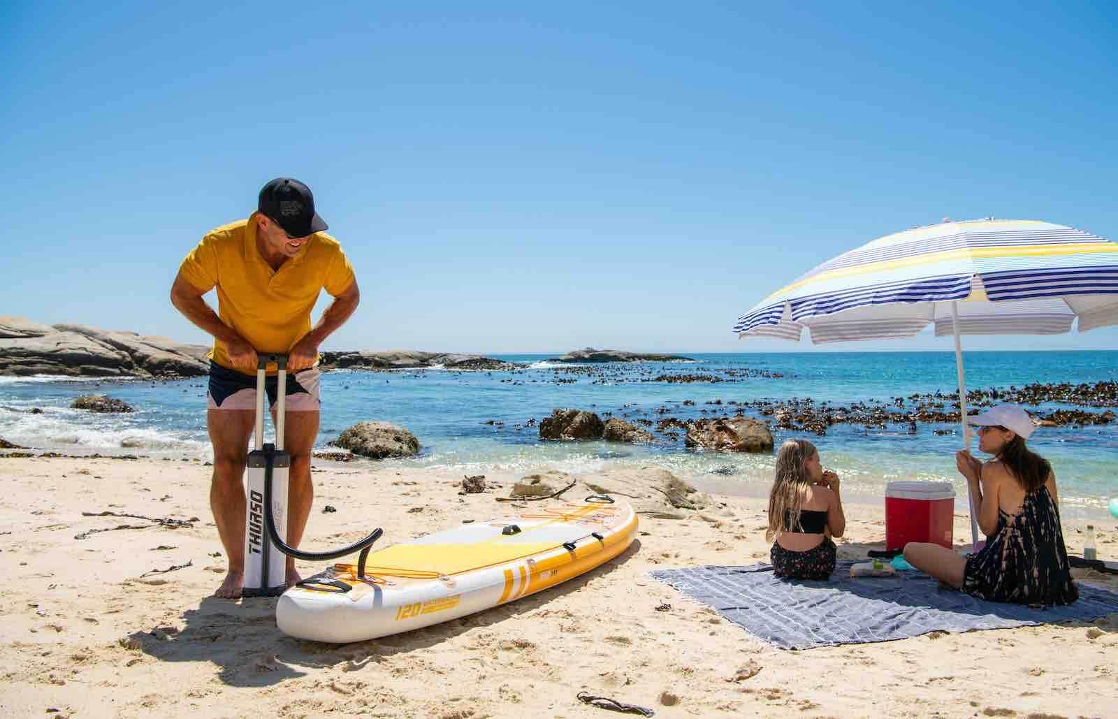man inflates Thurso Surf Waterwalker all-around SUP on beach near two people under an umbrella