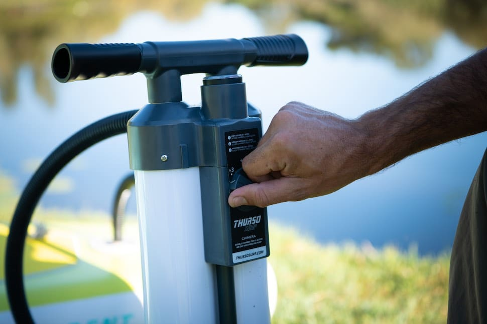 Closeup of man adjusting Thurso Surf air pump for inflatable stand up paddleboards