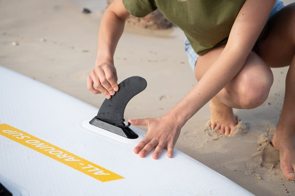 Closeup of woman attaching fins to a Thurso Surf Waterwalker all-around SUP