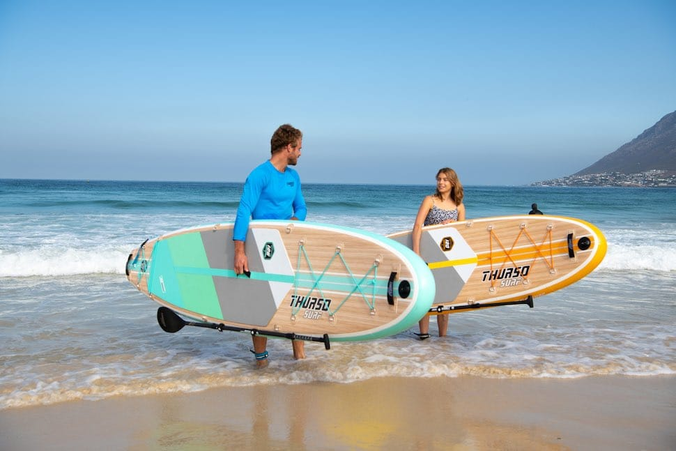 Man and woman walk along beach with Thurso Surf Waterwalker All-around SUPs