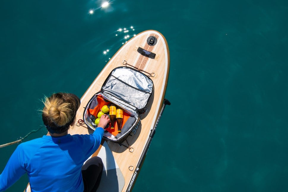 Woman kneeling on her Thurso Surf iSUP reaches into her deck cooler bag for a snack