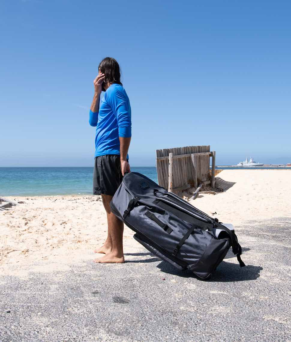 Man standing on footpath near beach with Thurso Surf roller backpack