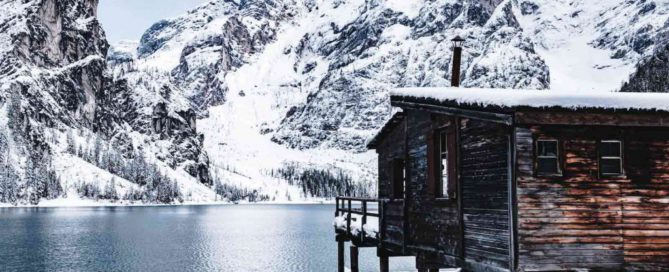 Wood cabin on stilts cabin overlooking lake and snow covered mountains