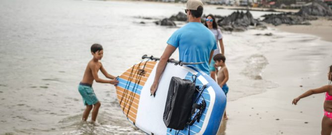 man walks with Thurso Surf Multipurpose SUP along beach with family