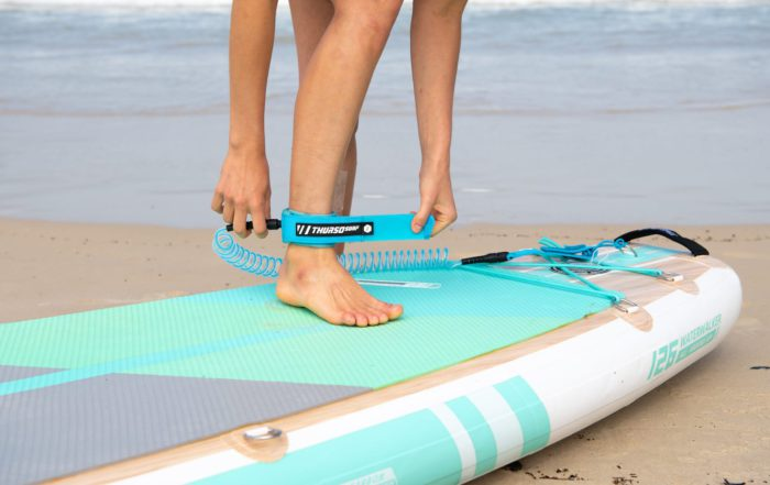 woman attaches ankle leash for SUP safety