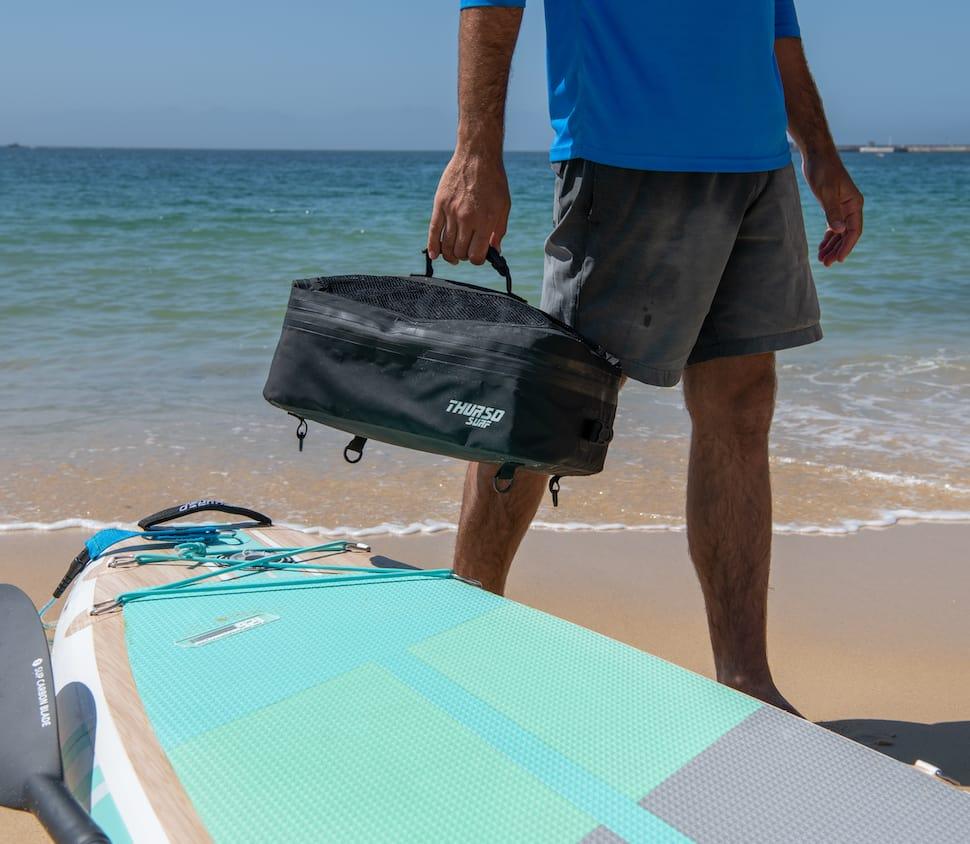man carries a Thurso Surf deck cooler bag on beach