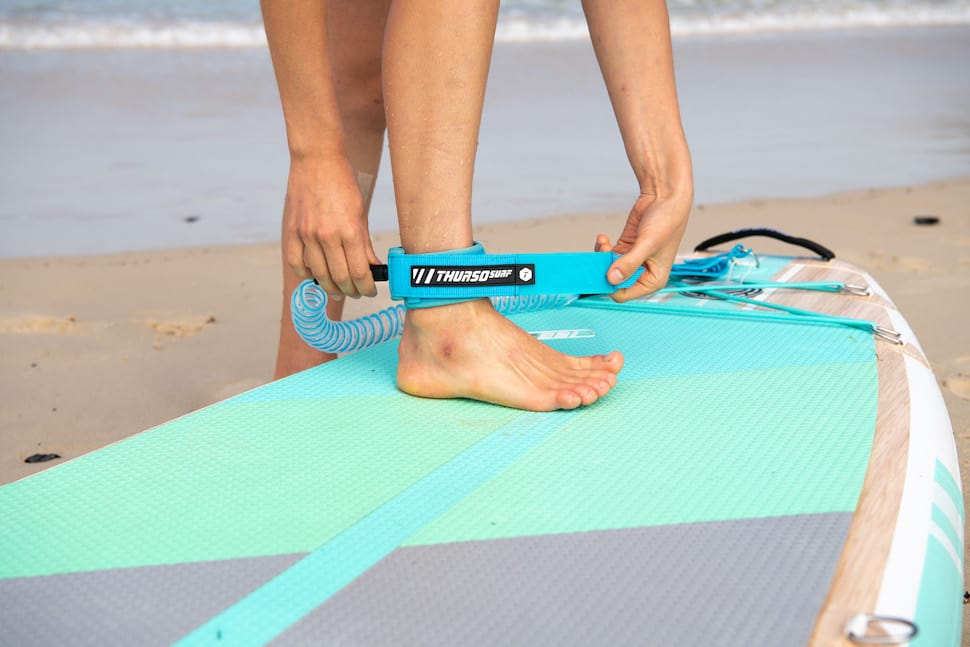 woman attaches Thurso Surf Waterwalker all-around ankle for SUP safety