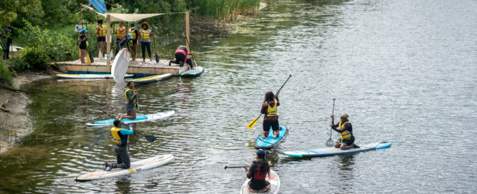 students taking a paddleboard lesson