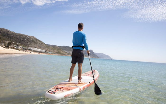 Man paddling away from the beach to do SUP fitness on a Thurso Surf Waterwalker all-around SUP