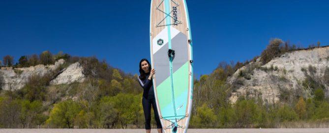 Woman holding Thurso SUP board upright