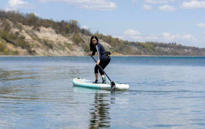 Woman doing a SUP turn on her Thurso Surf Waterwalker