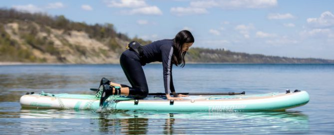 Woman crouching onto an inflatable stand up paddleboard