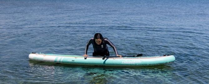 Woman demonstrating how to get back on a paddleboard after falling in the water