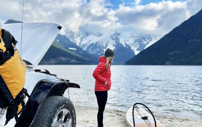 Woman standing in front of jeep on the beach with mountain and lake in the background while she waits for her Thurso Surf Waterwalker all-around SUP to inflate using an electric pump