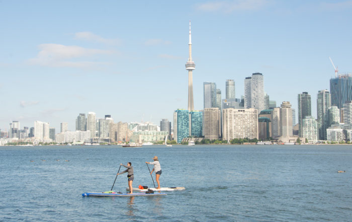 Two women paddleboard on Lake Ontario with the Toronto skyline in the background