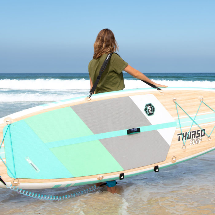 woman carrying paddle board with a shoulder strap carrier thurso surf