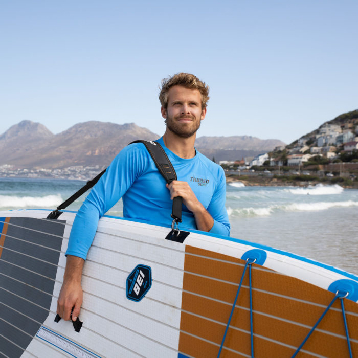 man carrying paddle board with a shoulder strap carrier thurso surf